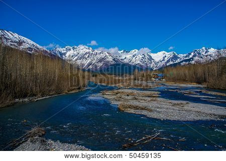 Azure Sky, Glacial Emerald River, and Snow Capped Mountains with a Small Alaskan Settlement