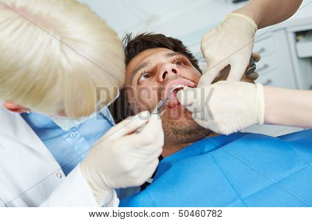 Dentist and dental assistant checking mouth of patient with toothache