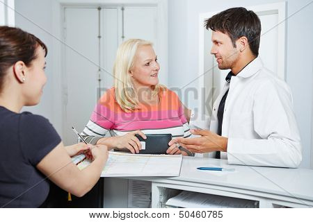 Doctor talking with senior woman at reception to say goodbye