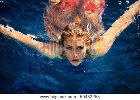 young woman in pool swimming looking at camera shot from above