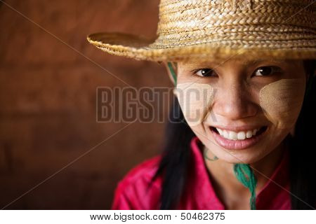 Portrait of beautiful young traditional Myanmar girl with straw hat smiling. Close up head shot.