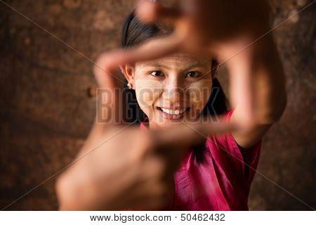 Beautiful young traditional Myanmar girl playing fun.