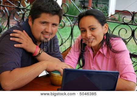 An Attractive Hispanic Couple Using A Laptop Computer Together