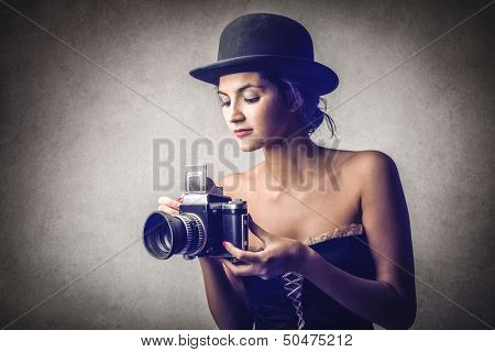 beautiful woman with vintage camera and bowler hat