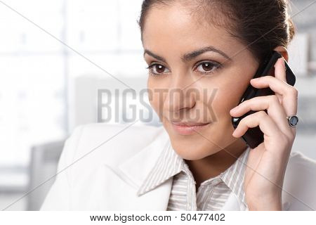 Closeup portrait of businesswoman listening to mobile phone call, smiling.