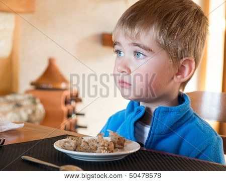 Grievous little boy sitting behind table with full plate