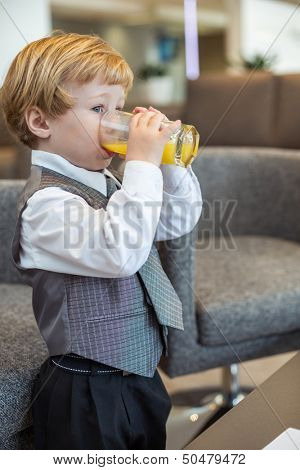 A little boy in a business clothes drinking juice in the business center
