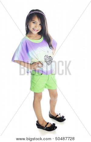 A beautiful young elementary girl happily waring her too-big sister's shoes.  On a white background.