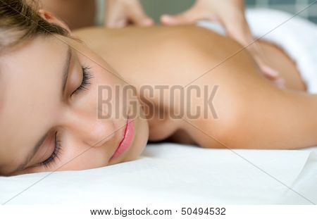 Beautiful young woman having a massage in a spa