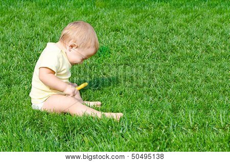 Pretty baby sneezes sitting on a grass