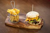 Close up on a cheese burger and french fries served in classy restaurant on a wooden board