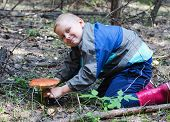 stock photo of face-fungus  - The joyful boy has found an big aspen mushroom in wood - JPG