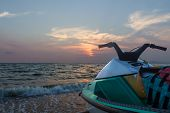 stock photo of ski boat  - Jetski parked on a beach against blue sky and sunset - JPG
