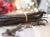 stock photo of cardamom  - Vanilla pods with spices like cardamom cinnamon and gleaming holiday lights - JPG