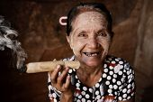 Happy old wrinkled Asian woman smoking traditional tobacco. Bagan, Myanmar.