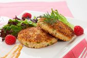 picture of cooked crab  - Two crab cakes appetizer garnished with spicy sauce green salad and raspbery - JPG