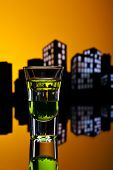 picture of absinthe  - Absinthe shot in nice colorful cityscape setting - JPG