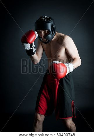 Man In Helmet Boxing In Black Background