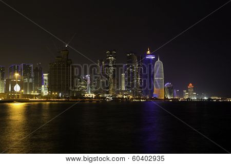 A night view of the towers in Doha's business district, which are lit up as dusk falls.