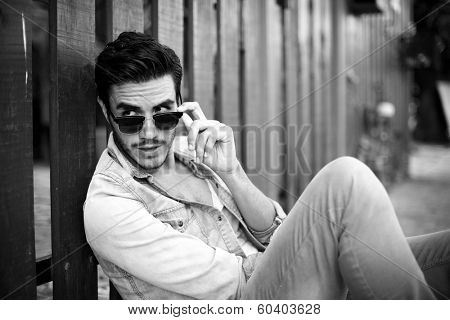 Pensive man sitting outdoors, looking through his dark glasses