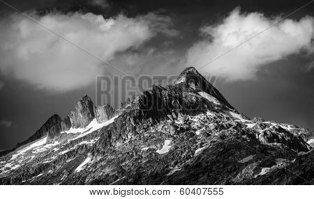 Black and white photo of majestic mountainous landscape, dramatic cloudy sky, beautiful panorama, extreme adventure and traveling concept