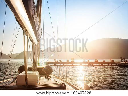 Sailboat on sunset, luxurious water transport, bright sun light on the sea, evening travel on sail yacht, summer vacation, yachting sport concept