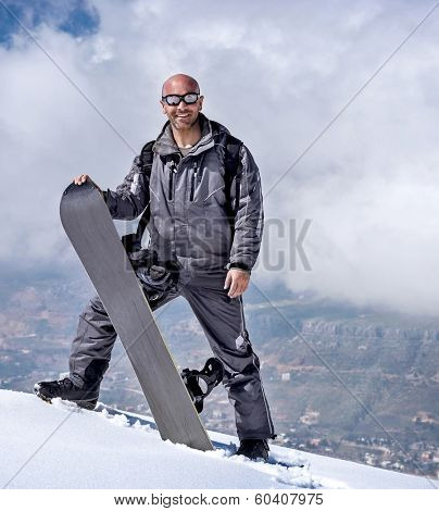 Male snowboarder in the mountains, standing on the top of mountain and holding in hands snowboard, wintertime sport, winter vacation concept