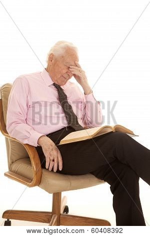 Elderly Man Pink Shirt Hand On Head Book