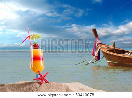 Fresh Cocktail on the beach in Thailand with Long tailed boat on background