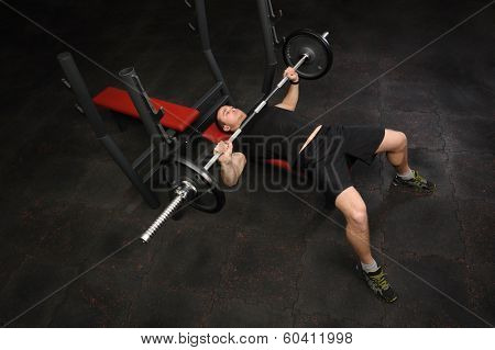 Handsome young man doing bench press workout in gym. Copy space at left lower corner.