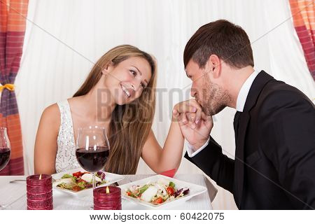 Man Kissing A Womans Hand At A Romantic Dinner