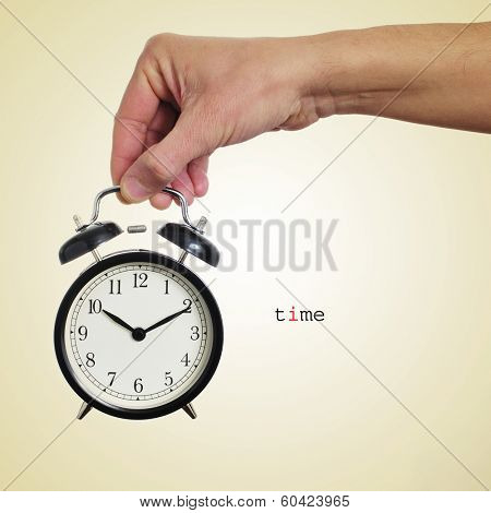 someone holding a typical mechanical alarm clock and the word time written in a beige background with a retro effect