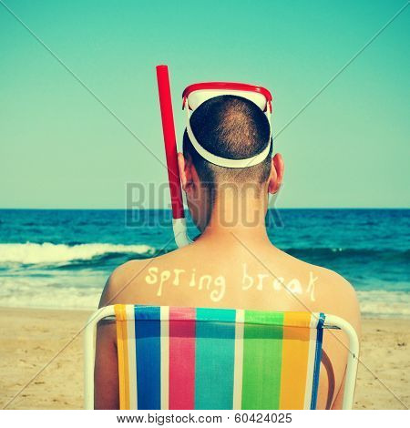a man wearing a diving mask and a snorkel seated in a deckchair on the beach with the text spring break written in his back as a tan mark, with a retro effect