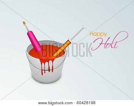 Indian festival Happy Holi celebrations concept with colour bucket and pichkari on grey background.