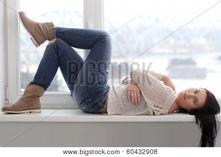 Cute, beautiful brunette on the window sill