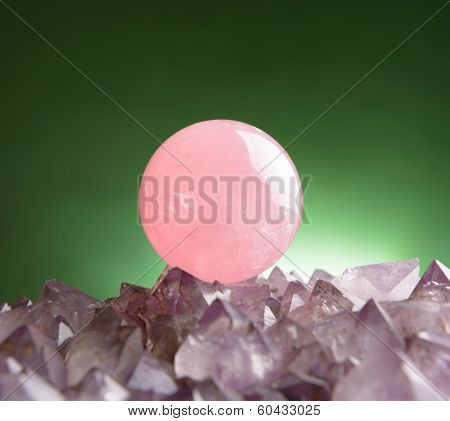 Sphere of rose quartz natural crystal on amethyst rock