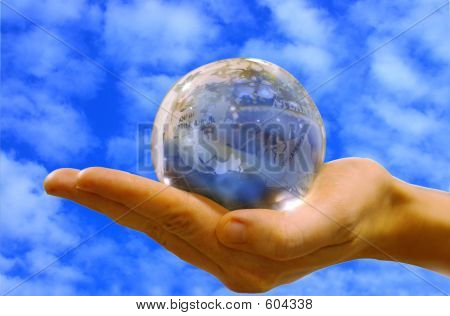 Hand Holding Glass Globe With Sky