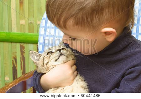 Cute boy and kitten looking at each other's eyes