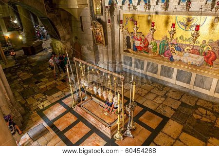 JERUSALEM. ISRAEL - AUGUST 21, 2013: Stone of Anointing and mosaic icon on the wall at the entrance to Holy Sepulcher church designate the place where Jesus' body was prepared for burial.