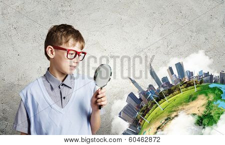 Cute school boy examining objects with magnifying glass. Elements of this image are furnished by NASA