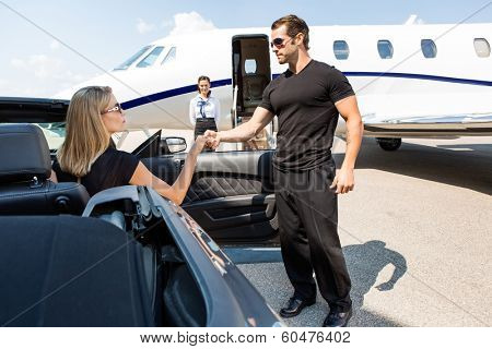 Bodyguard helping elegant woman stepping out of car at airport terminal