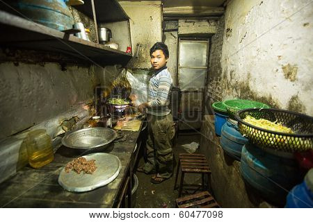 KATHMANDU, NEPAL - DEC 5, 2013: Unidentified boy from poorer area working in the kitchen dining room. About 2.6 million children in Nepal should work to ensure the survival of family.