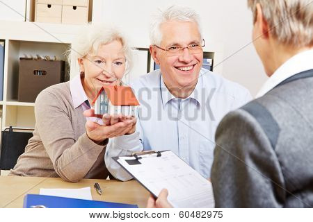 Happy senior couple with little house buying real eastate in office