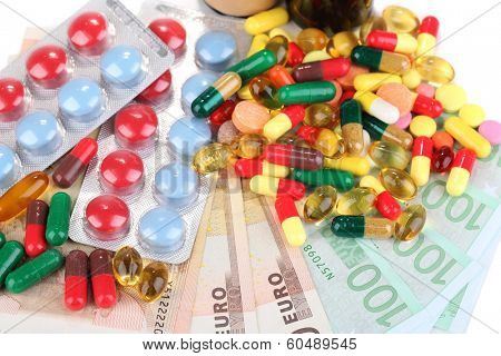 Prescription drugs on money background representing rising health care costs. Close-up
