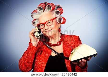 Portrait of an elderly woman in curlers talking on the phone.