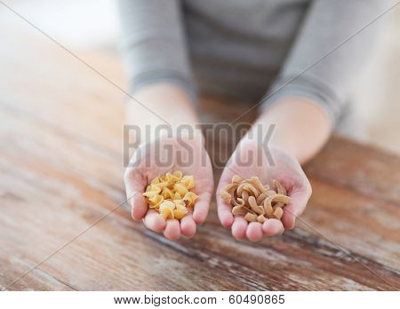 cooking, food and home concept - cloes up of female cupped hands with different pasta variations