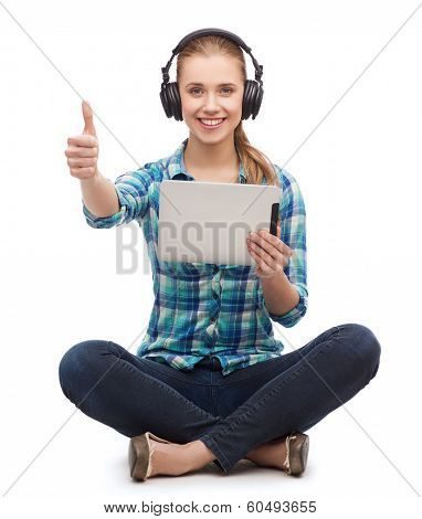 technology and internet concept - smiling young woman sitiing on floor with tablet pc computer and headphones and showing thumbs up