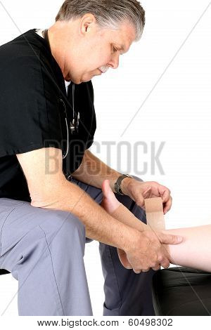 Mature Medical Doctor Wrapping Patients Ankle