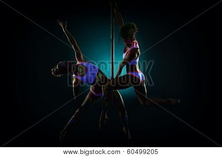 Pair of sexy pole dancers under UV light