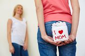 Close-up of teenage girl in jeans holding giftbox for mom behind her back